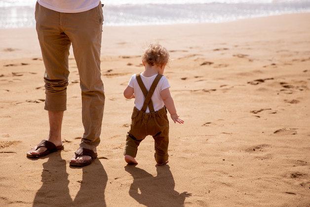 Klein jongetje op het strand met vader