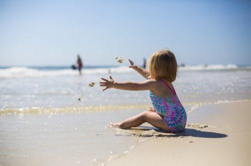 Klein meisje zit in het zand aan zee