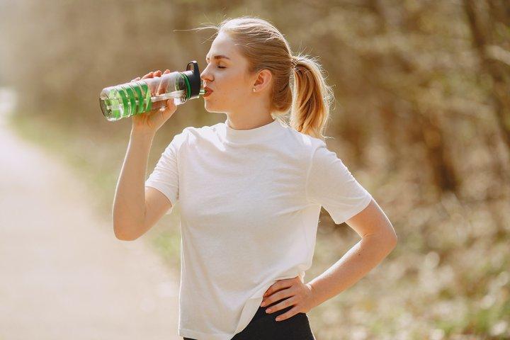 vrouw staand drinkt uit glazen fles