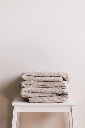 Drie handdoeken op een wit krukje
