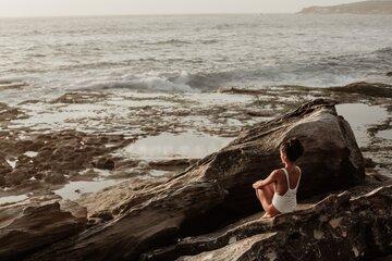 Vrouw zit op rotsen en kijkt uit op zee
