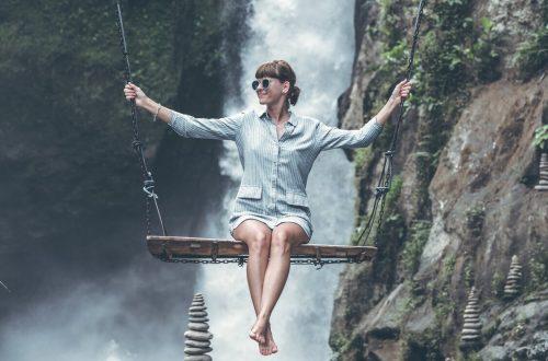 Vrouw op schommel met waterval op achtergrond