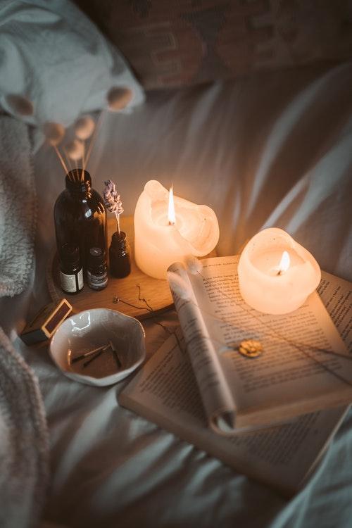 Kaarsen op bed met boeken